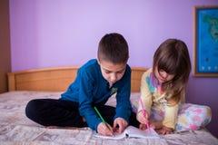 Fratello e sorella disegno di Having Fun al letto Fotografia Stock