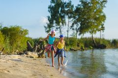 Fratello e sorella fatti funzionare lungo la spiaggia Festa e concetto di viaggio fotografie stock libere da diritti