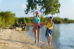 Fratello e sorella fatti funzionare lungo la spiaggia Festa e concetto di viaggio immagine stock
