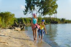Fratello e sorella fatti funzionare lungo la spiaggia Festa e concetto di viaggio fotografia stock libera da diritti