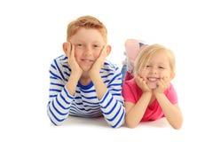 Fratello e sorella felici insieme contro fondo bianco Immagine Stock