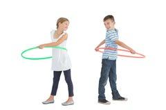 Fratello e sorella sorridenti che giocano con il hula-hoop Fotografia Stock Libera da Diritti