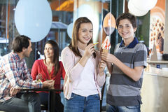 Fratello e sorella sorridenti che hanno gelato alla vaniglia in salone fotografia stock libera da diritti
