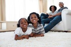 Fratello e sorella sorridenti che si trovano sul pavimento Immagine Stock Libera da Diritti