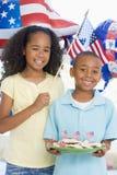 Fratello e sorella sul quarto di luglio con le bandierine Immagini Stock Libere da Diritti