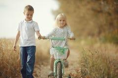 Fratello e sorella sulla strada di autunno Fotografia Stock