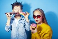 Fratello felice e sorella della famiglia che mangiano le guarnizioni di gomma piuma su fondo blu, cibo di concetto della gente di fotografia stock