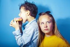 Fratello felice e sorella della famiglia che mangiano le guarnizioni di gomma piuma su fondo blu, cibo di concetto della gente di immagini stock libere da diritti