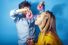 Fratello felice e sorella della famiglia che mangiano le guarnizioni di gomma piuma su fondo blu, cibo di concetto della gente di fotografie stock