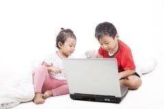 Fratello germano asiatico che per mezzo del computer portatile Fotografie Stock Libere da Diritti