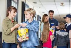 Fratello Giving Movie Tickets alla sorella At Cinema Fotografie Stock