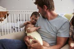 Fratello neonato In Nursery di With Son And del padre immagine stock