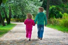Fratello piccolo e sorella che camminano dal sentiero per pedoni Fotografie Stock Libere da Diritti