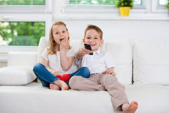 Fratello piccolo e sorella che guardano TV Fotografia Stock
