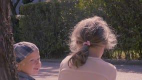 Fratello piccolo e sorella che si siedono sulla via in parco video d archivio