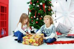 Fratello piccolo e sorella vicino ad un albero di Natale con una sorpresa Fotografia Stock Libera da Diritti