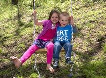 Fratello And Sister che gioca su un'oscillazione Fotografia Stock