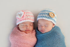 Fraternal Twin Baby Brother and Sister. Five week old sleeping boy and girl fraternal twin newborn babies. They are wearing crocheted pink and blue striped hats royalty free stock photo