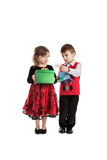 Fraternal twins with Christmas presents. Portrait of 3 year old fraternal boy and girl twins holding Christmas presents isolated on white background Royalty Free Stock Photos