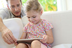 Frather showing her daughter how to use an adult's tablet stock photos