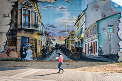 Fratii Buzesti street in Craiova, Romania. Craiova, Romania - September 16, 2016: Woman is walking near paņted wall on Fratii Buzesti street in Craiova, Romania Stock Photo