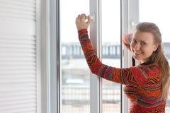 Frau öffnet ein Plastikfenster Stockfotografie