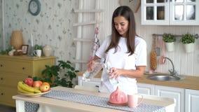 Frau öffnet Flasche, gießt Trinkwasser in Glas und trinkt es auf Küche, Zeitlupe stock video