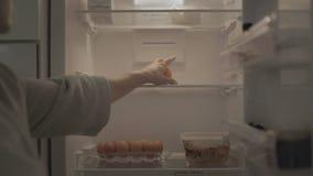 Frau öffnet weißen Kühlschrank und nimmt Zitrone aus Kühlschrank heraus stock footage