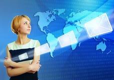 Frau über der Weltkarte, die E-Mail-Nachricht sendet Stockfotografie