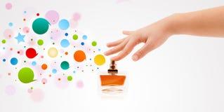 Frau übergibt bunte Sprühblasen von der schönen Parfümflasche Lizenzfreie Stockbilder
