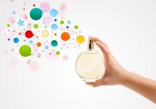 Frau übergibt bunte Sprühblasen von der schönen Parfümflasche Stockfoto