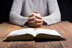 Frau übergibt das Beten mit einer Bibel in der Dunkelheit über Holztisch lizenzfreie stockfotografie