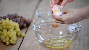 Frau übergibt das Brechen eines Eies, um Eiweiß und Eigelbe und Eierschalen am Hintergrund zu trennen stock video footage