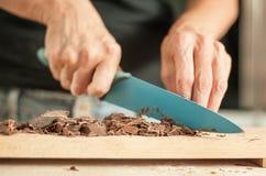 Frau übergibt das Hacken des Schokoladenblockes für feierlichen Kuchen lizenzfreies stockfoto
