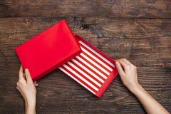 Frau übergibt das Halten der leeren Geschenkbox auf hölzernem Hintergrund Stockfoto