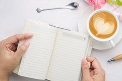 Frau übergibt das Halten des Notizbuches mit Stift und der Kaffeetasse auf weißem wo Lizenzfreie Stockfotos