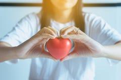 Frau übergibt das Halten des roten Herzens vom Patienten, Gesundheitswesen Konzept überprüfend Stockfotografie