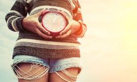 Frau übergibt das Halten eines roten Weckers, Zeitkonzept Stockfotografie