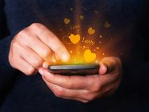Frau übergibt das Halten und die Anwendung des Smartphonemobiles oder -Handys für das Simsen oder -mitteilung für Valentinsgruß-T Lizenzfreies Stockbild