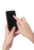 Frau übergibt den rührenden Smartphone, der auf weißem Hintergrund lokalisiert wird Lizenzfreie Stockbilder
