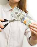 Frau übergibt den Schnitt des Dollarscheins mit Scheren Stockfoto