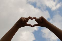 Frau übergibt die Herstellung einer Herzform auf Hintergrund des blauen Himmels Stockbilder