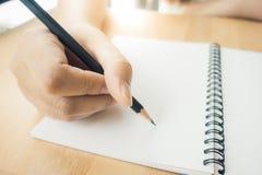 Frau übergibt Schreiben auf Buch im Büro Geschäftsfrau, die an Schreibtisch des Holzes arbeitet Stockfotografie