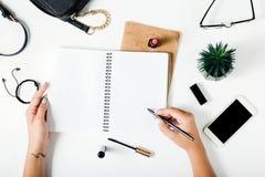 Frau übergibt Schreiben im Notizbuch auf weißer Tabelle mit weiblichen acces Stockfoto
