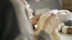 Frau übergibt Stricknadeln weißes Wollgewebe Strickgarn des Frauenhobbys stock video