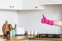 Frau übergibt tragende Schutzhandschuhe auf weißem Küchenhintergrund Konzept der sauberen Küche, erfolgreicher Daumen oben ja o.k lizenzfreies stockfoto