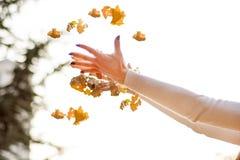Frau übergibt werfendes gefallenes trockenes Blatt in einer Luft am schönen Herbsttag lizenzfreies stockfoto