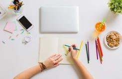 Frau übergibt Zeichnung im Büro des Notizbuches zu Hause Stockfotografie