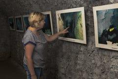 Frau überprüft eine Fotoausstellung in einer des dunklen Hallen Höhlen-Bären Safari Park in Gelendzhik, Krasnodar-Region, Russlan lizenzfreie stockbilder