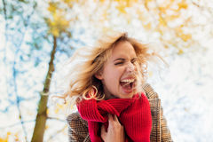 Frau in überprüftem Mantel lachend im Herbstpark stockfoto